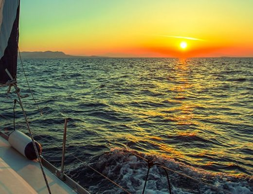 Sail trips in Chania, Crete. View of the setting sun from the deck of a sailing boat in the open sea